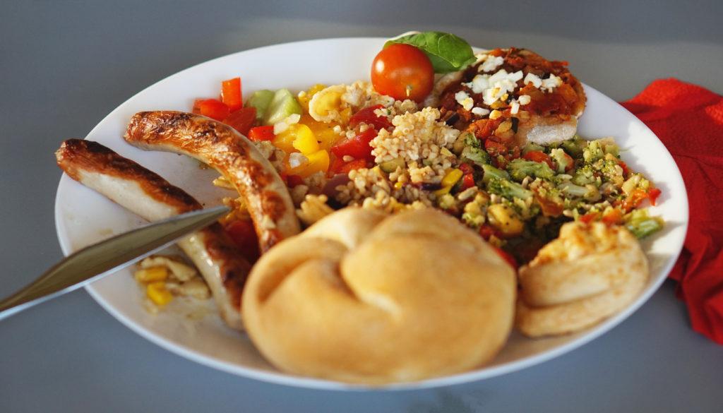 So sieht ein internationaler Grillteller aus: Bulgur aus Marokko, dazu peruanischer Quinua-Salat, Pizzaschnecken (ist doch italienisch) und Regensburger Grillwürste.